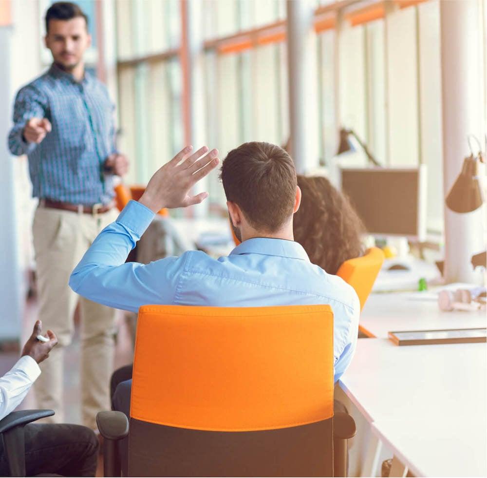 Man raising his hand in an HR team meeting held in a modern office.