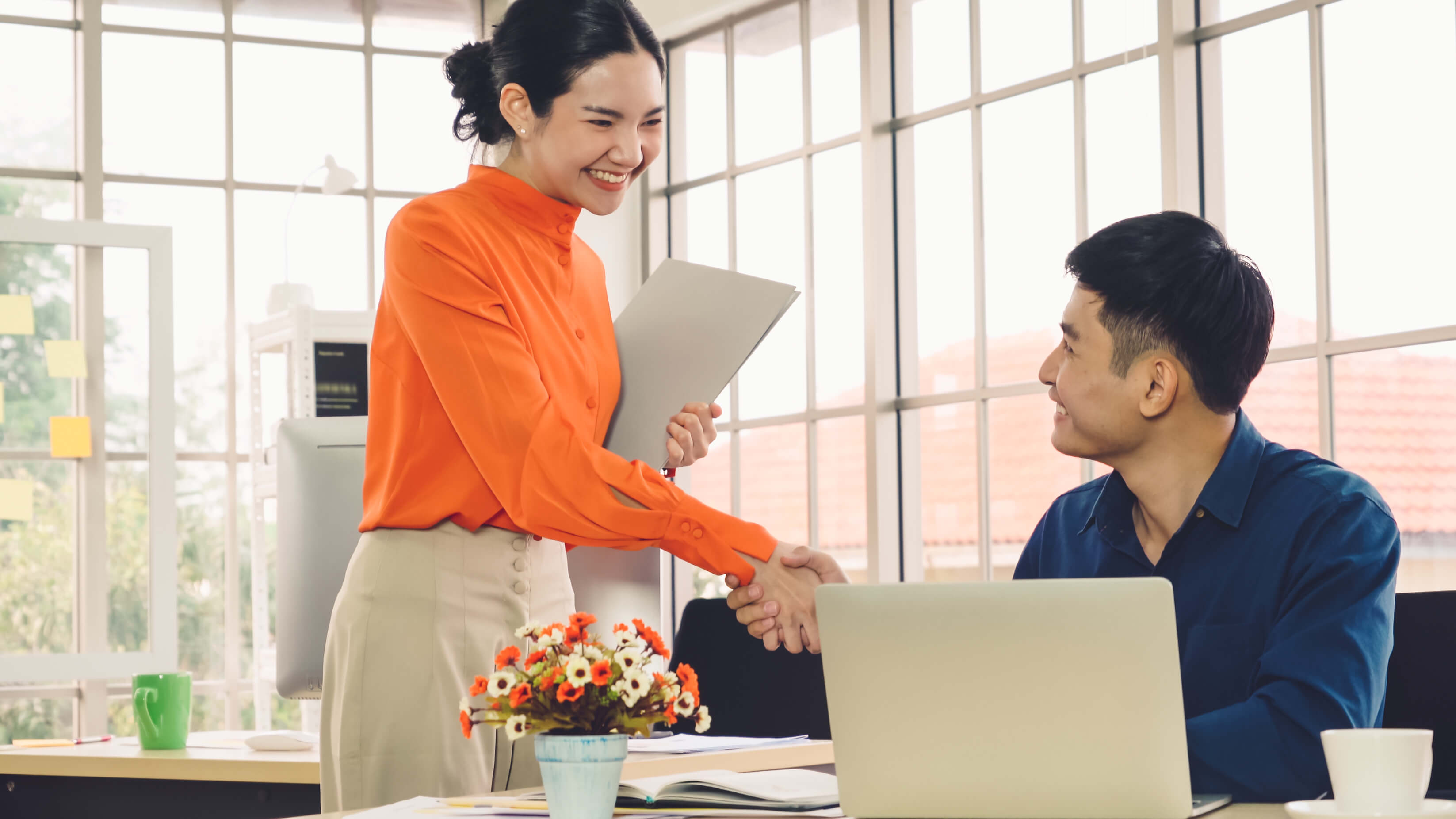 smiling woman shaking man's hand next to desk with laptop