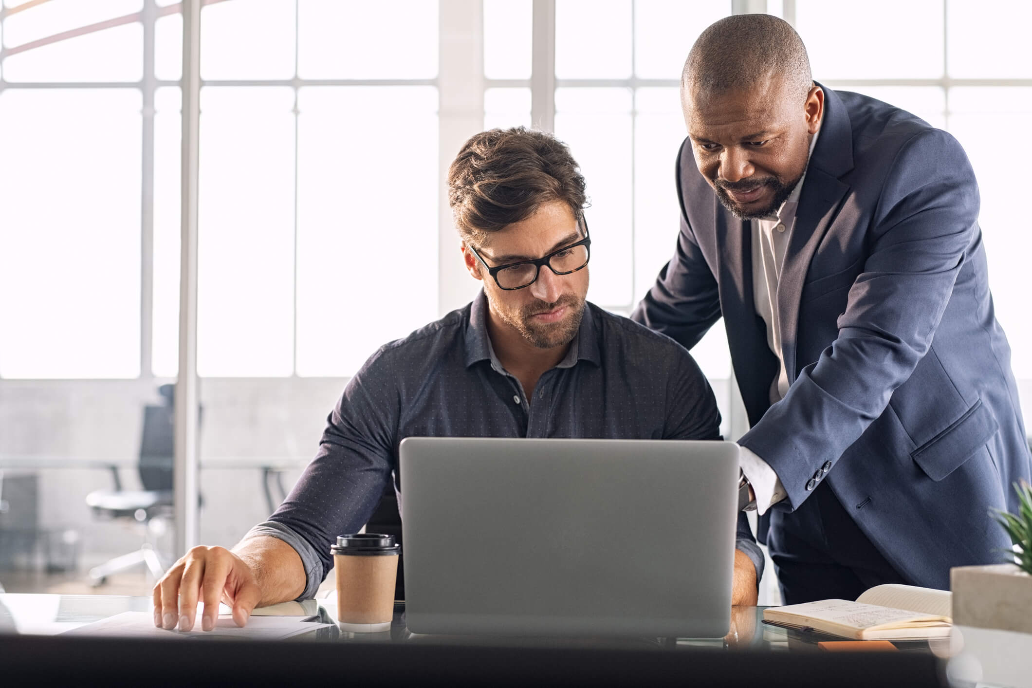 man showing another man how to use HR analytics at desk with laptop