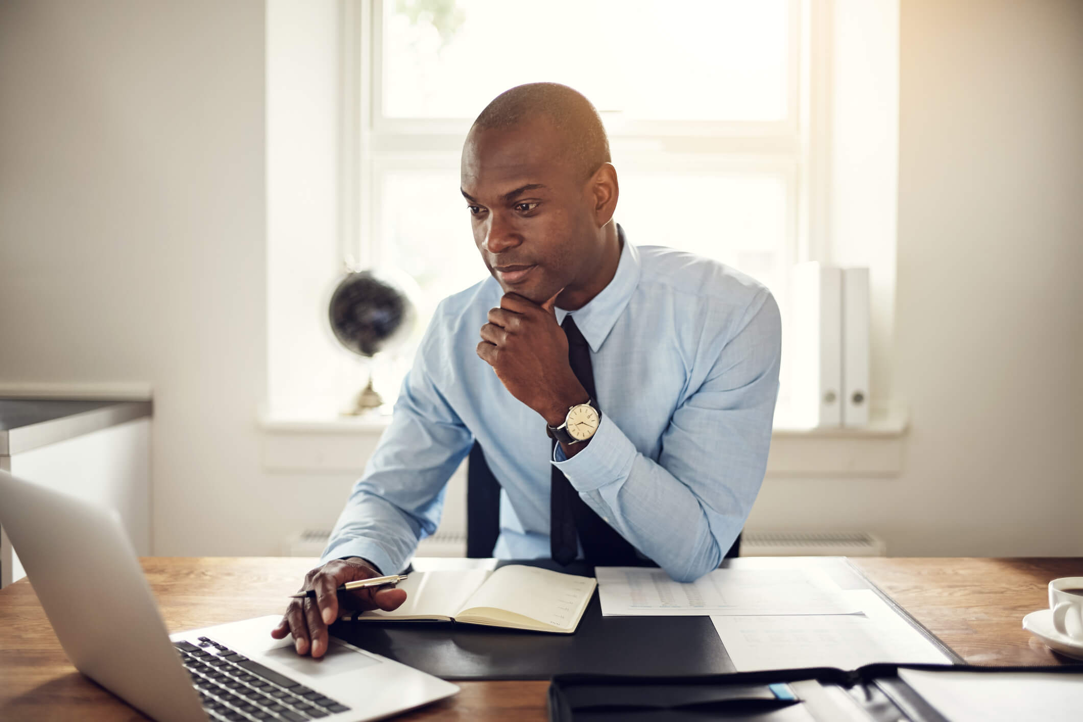 man at desk using a laptop for workforce time and attendance
